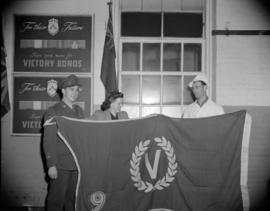 [Burns' Meats employee holding a victory bonds flag with a woman and a man in military uniform]