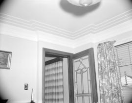 [Interior view of a room in a house showing the mouldings around the ceiling]
