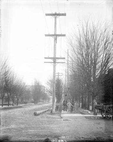 Men raising power poles at Burrard and Smithe Streets