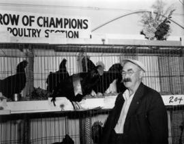 Man holding award-winning rooster in front of 1955 P.N.E. Poultry and Pet Stock competition &quot...