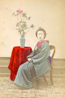 [Studio portrait of a woman in formal Japanese dress sitting in chair]