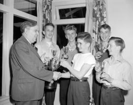 [Man presenting bowling trophies to a group of boys]