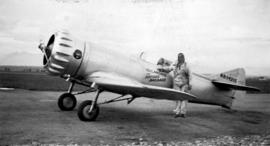 "[Pilot Earl Ortman beside] an experimental [air]plane named ""Gilmore the Record Breaker&quot..."