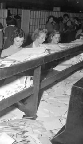 [Employees sorting mail at the post office]