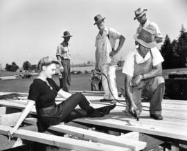 [Jean McKenzie takes a break from rehearsal as carpenters construct the Timber Bowl Stadium at Br...