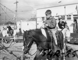 Young boy on pony by Livestock building in P.N.E. Kiddieland