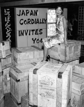 Catherine Arakawa atop crates imported from Japan for Salute to the Orient exhibit at the 1959 P....