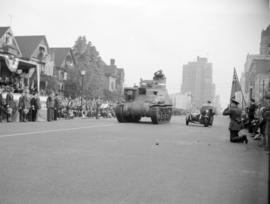[Armoured car passing crowds on Burrard Street during a military parade]