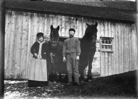 [Man and woman standing with two horses in front of barn doors]
