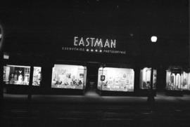 [Exterior of Eastman Photographic Ltd. lit up at night]