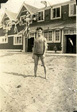 [Young man in swimsuit standing in front of Locarno Beach bathhouse]