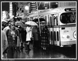 Christmas shoppers [group of people waiting in the rain to board the Victoria bus with people wal...