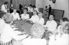 Group of women seated at table holding a piece of Centennial tartan fabric