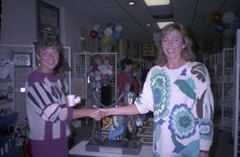 Two women shaking hands in front of gift display