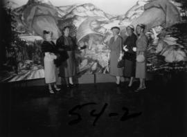 Ladies posing next to mural of British Columbia resources in P.N.E. B.C. building