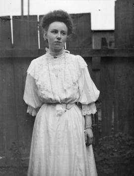 [Young woman in white dress, standing in front of a fence]