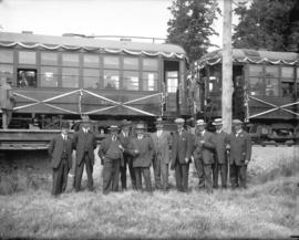 [Group of men assembled in front of interurban railway cars decorated for opening of Saanich Inte...