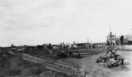 Construction site with equipment and railroad tracks visible, grain elevators in background
