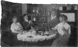 Four adults sitting around table drinking wine with small Christmas tree in centre
