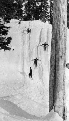 Figures sliding down snow-covered hill, Grouse Mountain