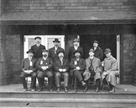[Unidentified group of men on porch of building]