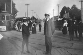 [A group of people standing on the street and disembarking from the Robson streetcar]