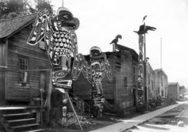 [Totem poles in front of longhouses]