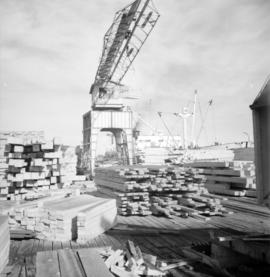 [View of the crane and piles of lumber at H.R. McMillan Co.]
