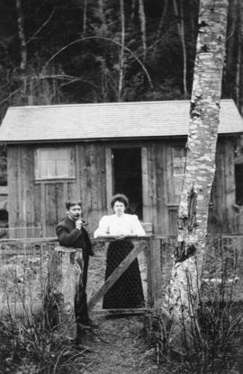 [Man and woman in front of cottage at] Britannia Beach