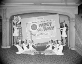 "[Women in sailor suits in front of a ""Meet the Navy"" movie poster in the Orpheum Theatr..."