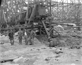 [Men standing next to trestle at Coquitlam Dam construction site]