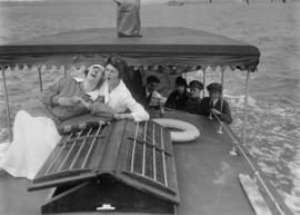 Two women on the deck of a boat with others behind