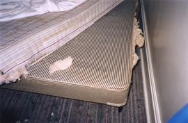 Damaged mattresses inside Columbia Hotel at 303 Columbia Street