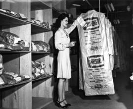 Nelson's Laundry staff person beside rack of packaged garments