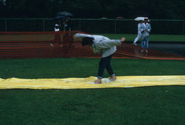 Man standing on slip and slide during the Centennial Commission's Canada Day celebrations