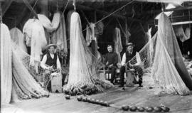 North Pacific Cannery [showing men repairing fishing nets]