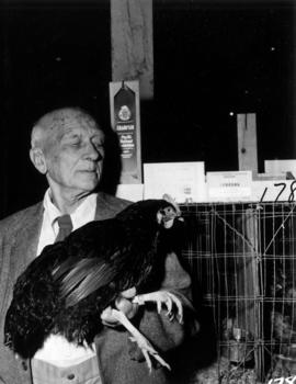 Man holding award-winning hen in 1955 P.N.E. Poultry and Pet Stock competition