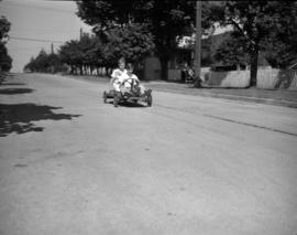 [Two boys riding down the street in a go-cart]