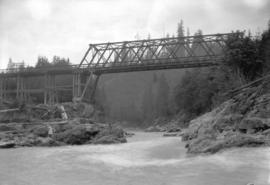 [Girl standing on rocks, below bridge on the Fraser River]
