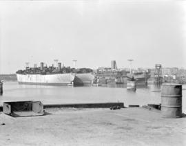 [Cargo ships and a passenger boat at dock]