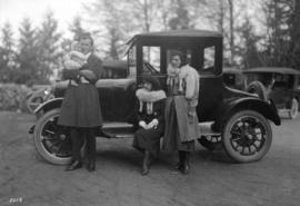 [Woman and a man with baby standing beside car - left hand drive]