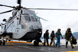 Torchbearer 290 Brett Rickard carries the flame lantern off of a helicopter onto the HMCS Vancouv...
