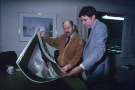 Toni Onley (left) and man examine his Centennial Art Series print at Agency Press