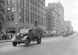 [A parade of military vehicles travelling west along Georgia Street]