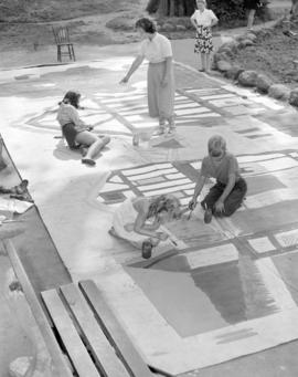 [Women and children painting a mural, probably as a back-drop for a play]
