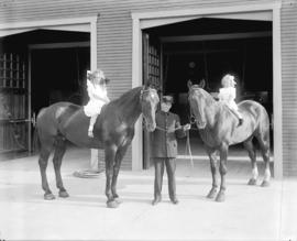 [Firehall no. 11 with fireman and girls sitting on horses]