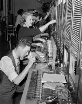 [B.C. Telephone technician working on equipment while switchboard operators work in the background]