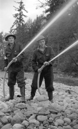 [Two A.R.P. firemen with water hoses at Lynn Creek]