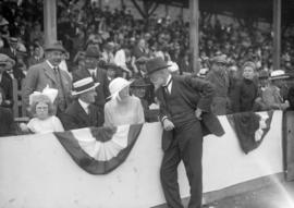 Gentleman talking to a woman in a grandstand