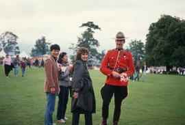 Mountie handing out Canada flags during the Centennial Commission's Canada Day celebrations